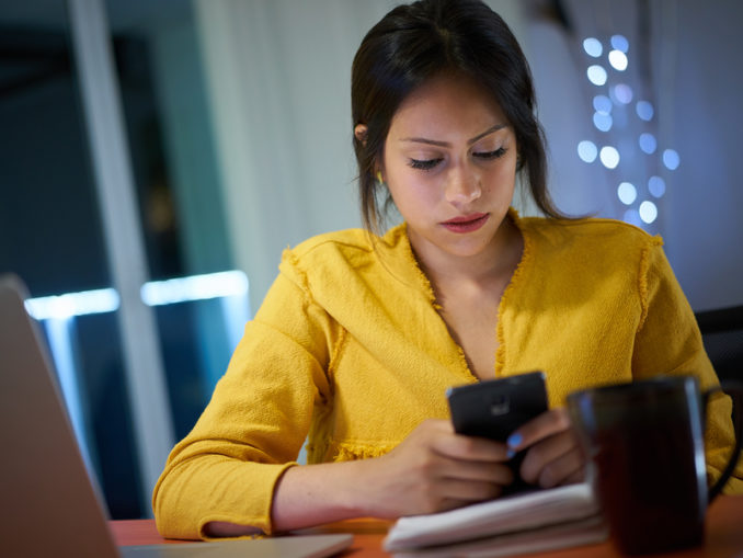 College Student Studying At Night Types Message On Phone